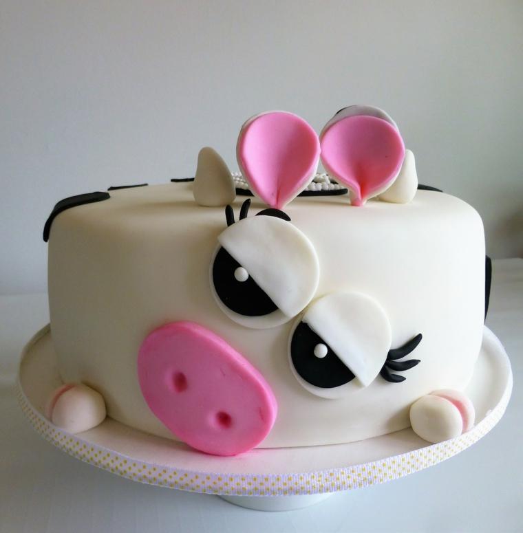 Torte di compleanno particolari, forma rotonda rivestita con pasta di zucchero bianca e decorata con la faccia di mucca