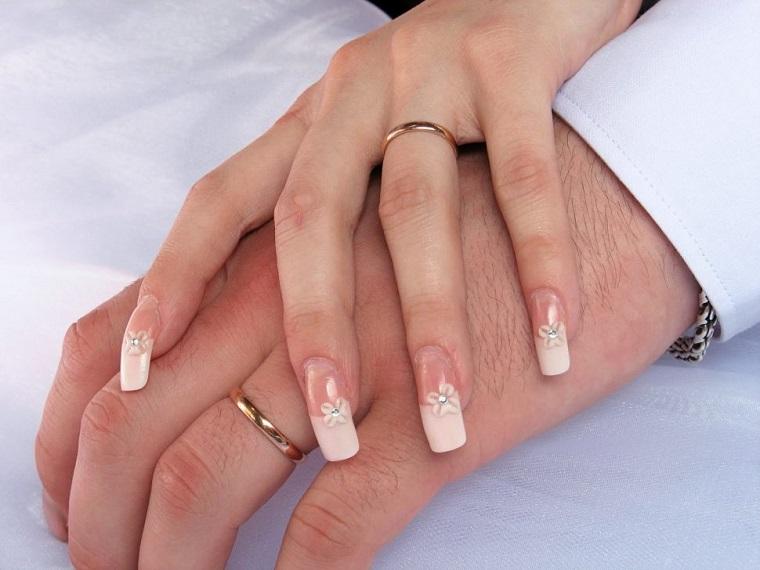 Mani uomo e donna con anelli in oro, unghie gel particolari, decorazioni manicure con piccoli brillantini e disegni floreali