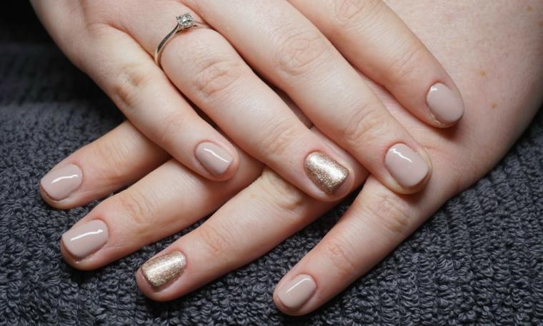 esempio di unghie color carne con l'anulare dorato, mani ben curate con un anello