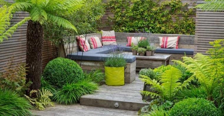 Arredo giardino con mobili in pallet e una cuscineria di colore grigio, tante piante sempreverdi