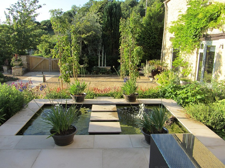Come abbellire un giardino, un laghetto artificiale con piante in vasi intorno