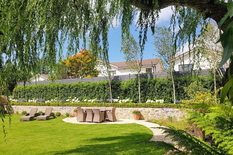 Arredo giardino con set tavolo da pranzo da esterno in rattan, due sdrai e una siepe intorno