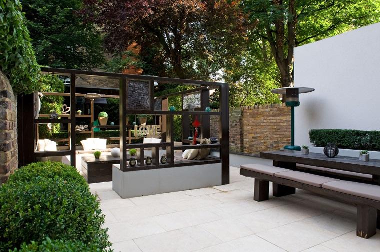 Piccoli giardini, arredamento con mobili in legno e una parete divisoria, siepe e alteri che fanno ombra