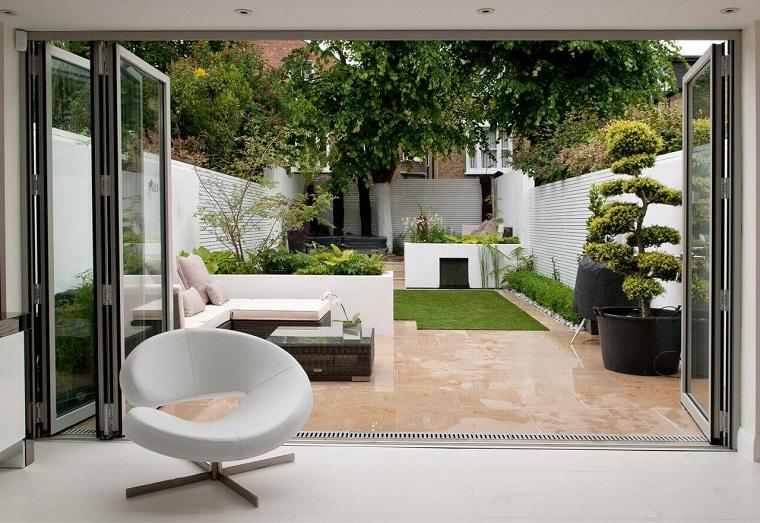 Arredo giardino con un divano in rattan e e tavolino, prato finto e alberi che fanno ombra
