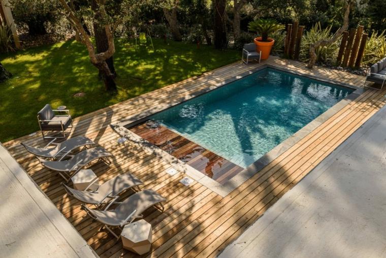 Piscina con bordi in legno, sdrai all'ombra, tanti alberi e piante sempreverdi