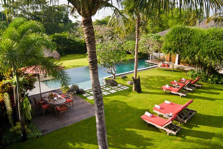 Come abbellire un giardino, piscina rettangolare con sdrai in legno e cuscineria di colore rosso
