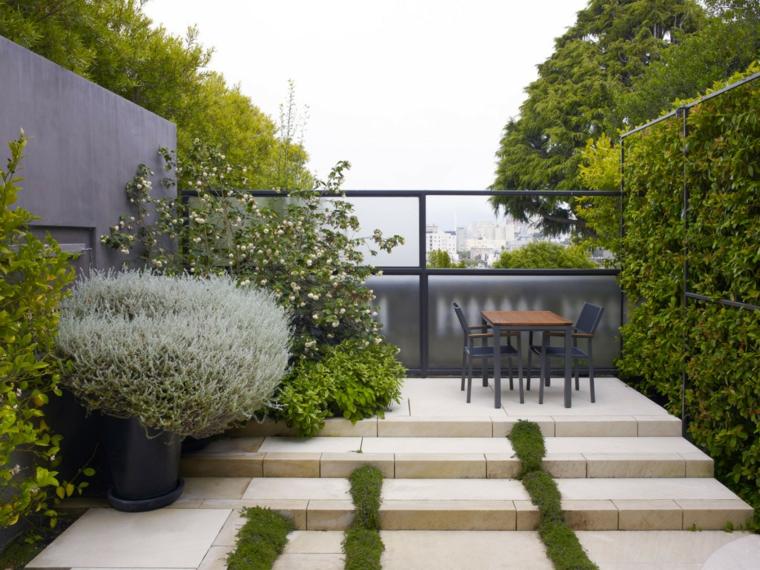 Recinzione giardino con siepe verde, pavimento in cemento e set di mobili in legno da esterno