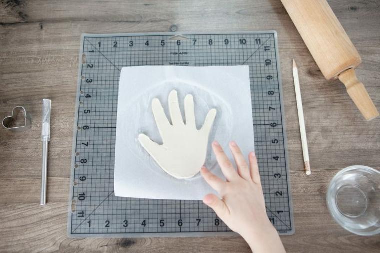 impronta della mano terminata, mano del bambino e attrezzi usati, mattarello, formina a cuore, matita