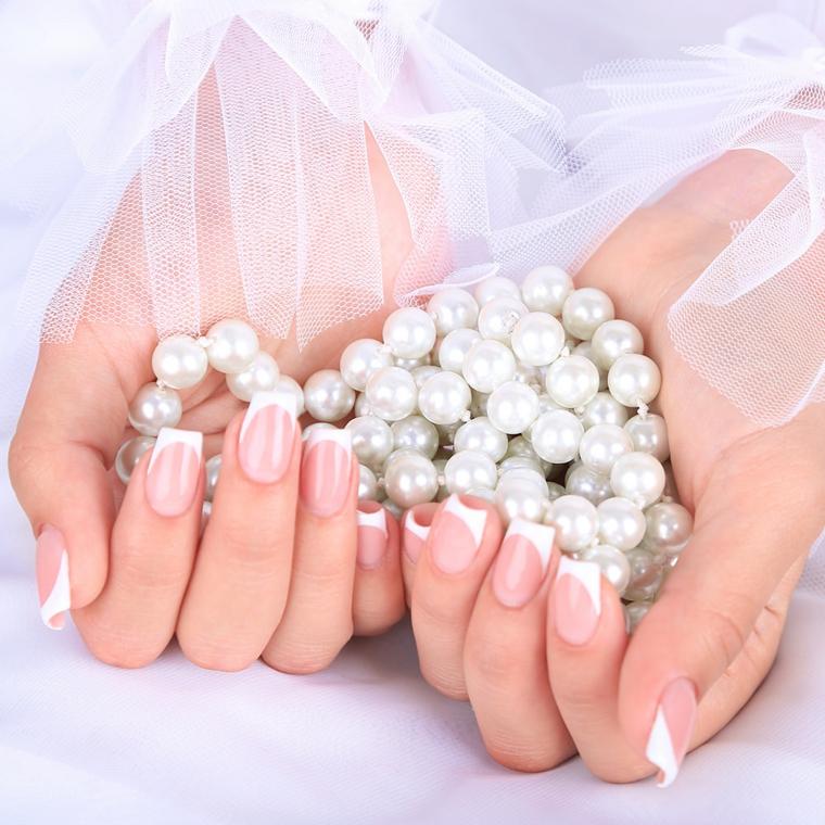 Unghie gel french bianco, collana di perle in mano della sposa con un velo bianco
