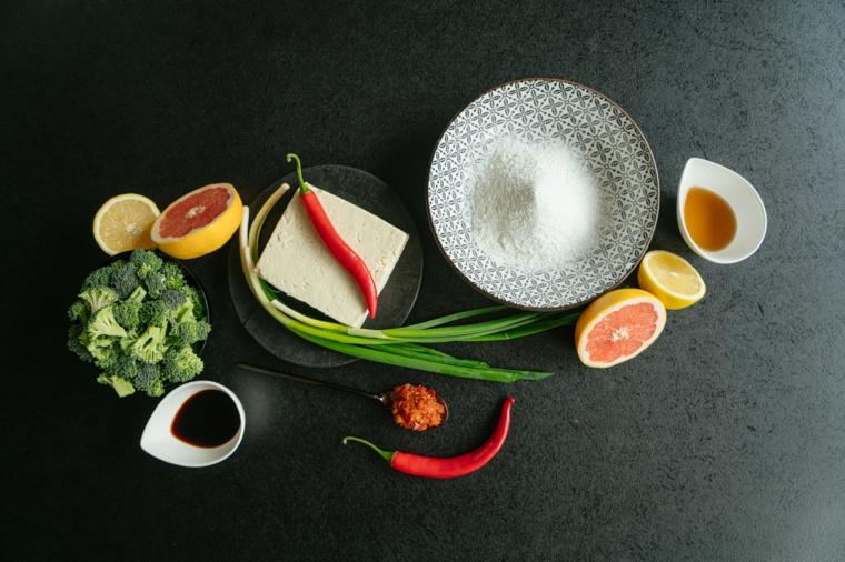 Tofu in padella, foto con ingredienti su un tavolo nero, ciotola con broccoli