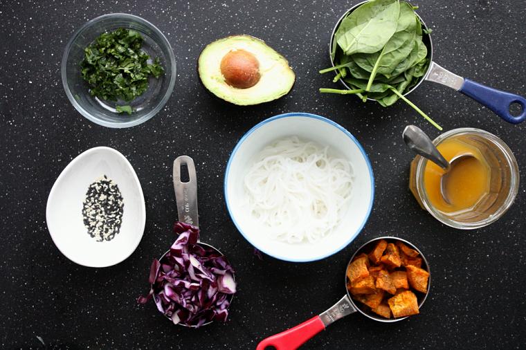 Idee per cena, ingredienti in ciotole per una ricetta, spaghetti di riso e avocado tagliato a metà