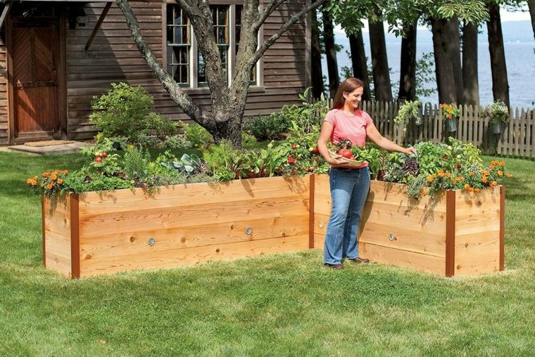 giardino con dei grandi vasi in pallet contenenti diverse specie di piante