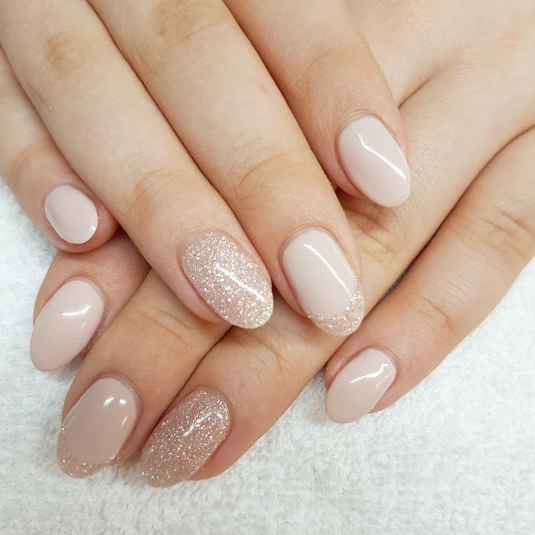 mani dal look naturale con uno smalto nude e anulare decorato con dei glitter