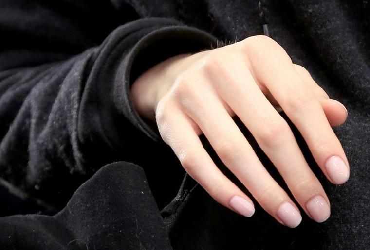 proposta di tendenza unghie color cipria con top coat lucido maglia nera a manica lunga