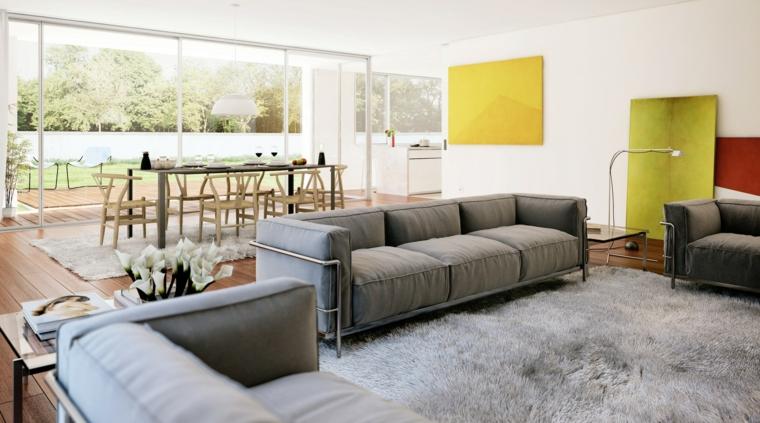 open space con un'ampia zona soggiorno composta da tre divani grigi, tavolo da pranzo e ampia vetrata