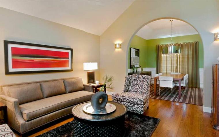 soluzione per arredare cucina soggiorno open space con un divano angolare, parete con arco e tavolo da pranzo