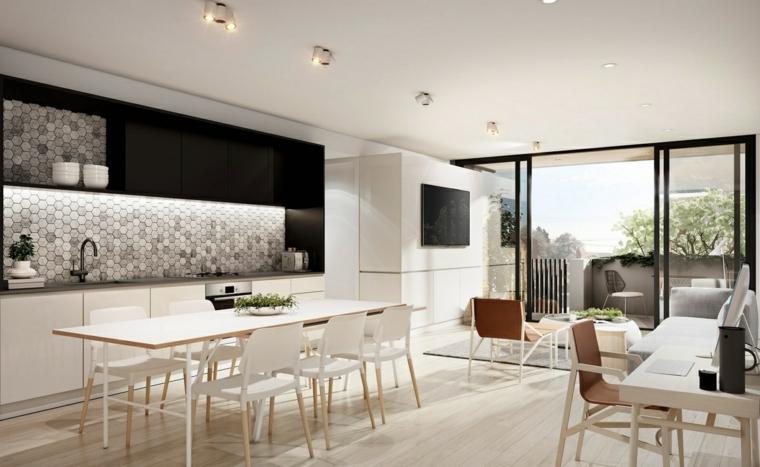 soluzione open space con cucina a vista, tavolo da pranzo, zona studio e soggiorno tutto in toni neutri