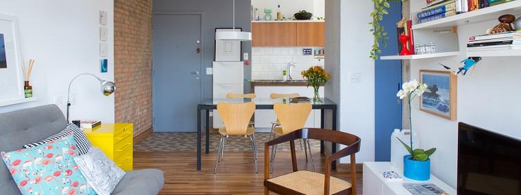 Cucina open space, tavolo da pranzo rettangolare con superficie di vetro, piccolo soggiorno con divano e parete attrezzata