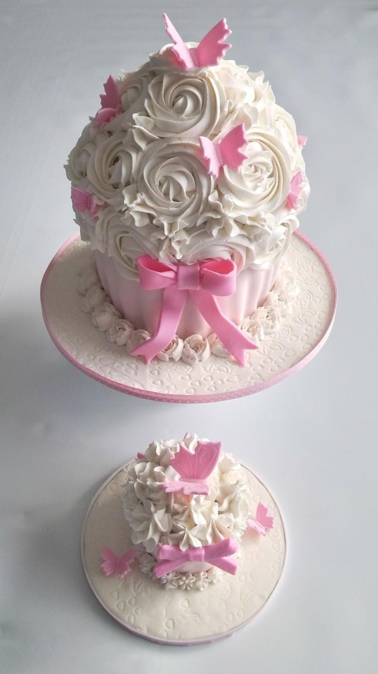 Due dolci uguali a forma di muffin, decorazioni torte con panna montata di colore bianco e farfalle rosa
