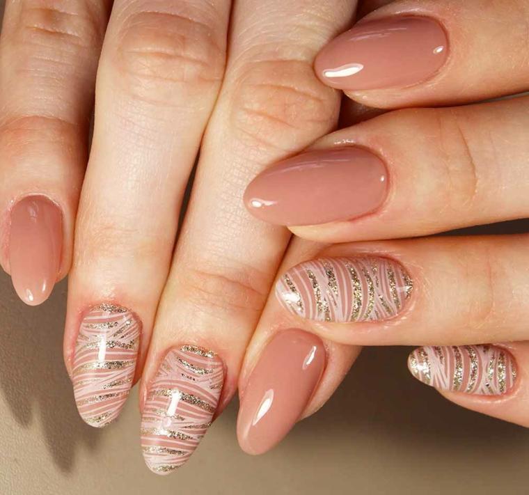 unghie dalla forma a mandorla, unghie gel color carne con alcune decorazioni con smalto bianco e glitter