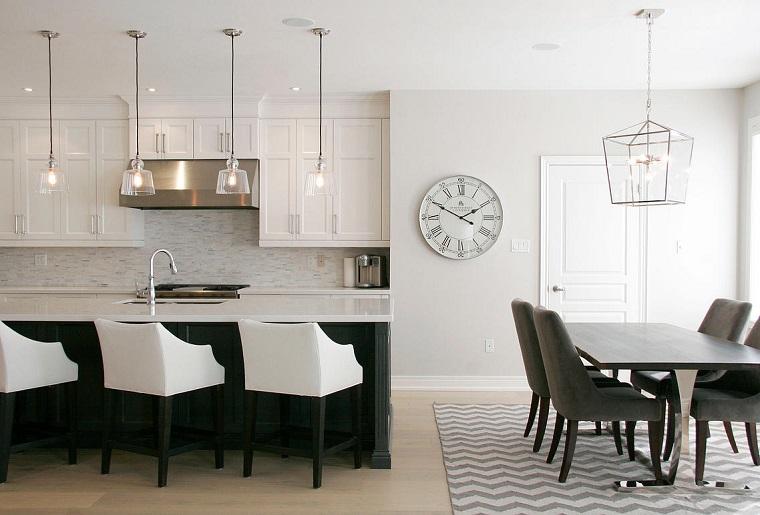 Cucina con mobili di legno e isola centrale, set tavolo da pranzo in legno e sedie in tessuto