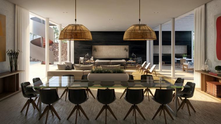 tavolo da pranzo in cristallo con tante sedie di design, lampade a sospensione a campana e zona soggiorno con parete nera