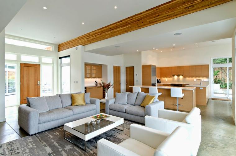 open space moderno con due divani grigi, due poltrone bianche e cucina a vista in legno