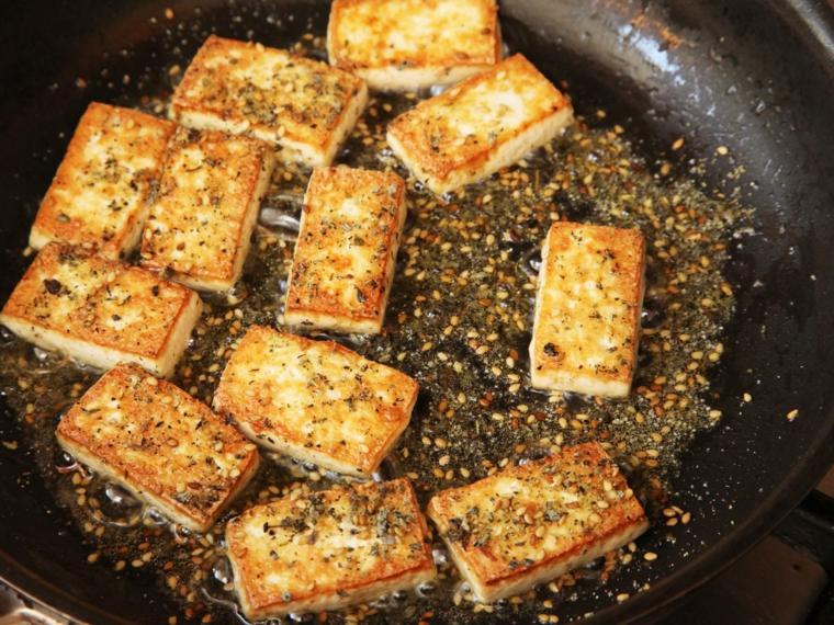 sesamo e fette di todu dorate, rosolate in una padella per delle ricette con tofu