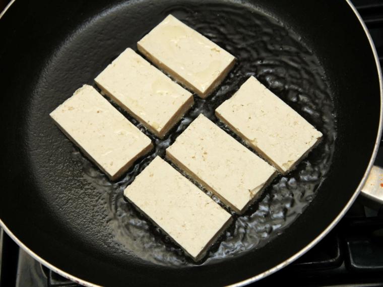 fette di tofu che rosolano in una padella con dell'olio vegetale per tofu ricette