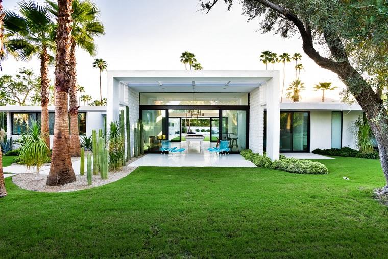 Come abbellire un giardino, casa moderna con un'area esterna con prato verde e palme