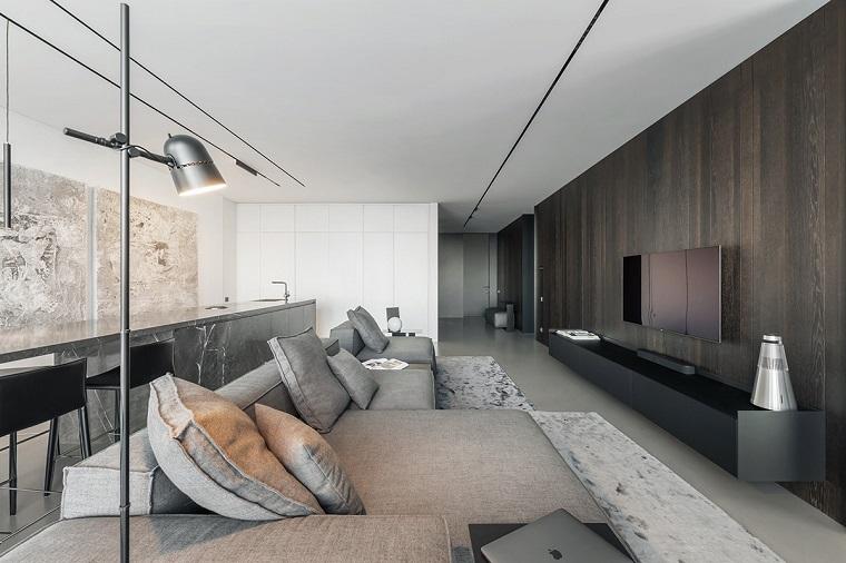 Sala da pranzo e salotto insieme, divano di colore grigio, parete rivestita di legno