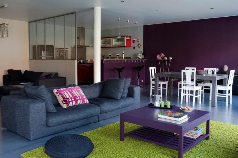 stanza moderna e colorata con una parete viola, divano blu, tappeto verde e tavolo viola