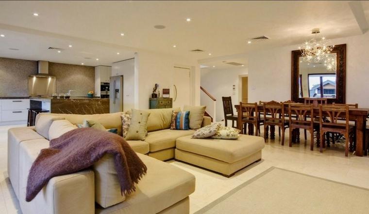 ampio open space con tavolo rettangolare in legno per il pranzo, divano a u contanti cuscini e cucina a vista
