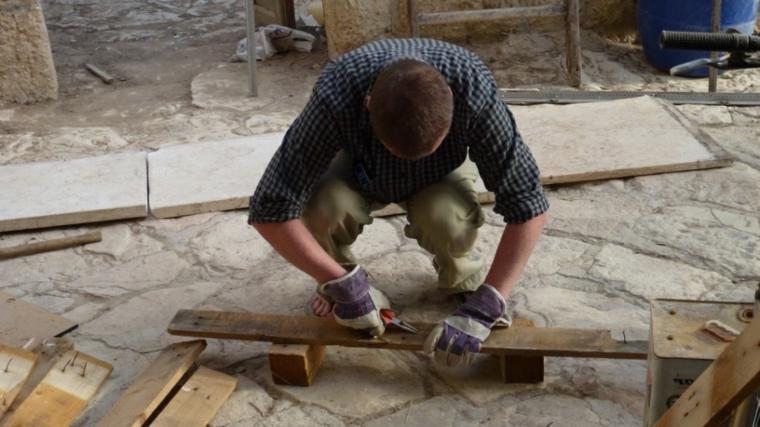 con una pinza, un uomo toglie dei chiodi dalle assi di legno per creare un pallet arredamento