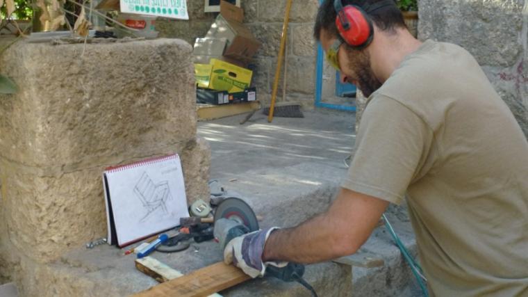 uomo intento a tagliare un'asse di legno: fase della realizzazione di mobili con pallet