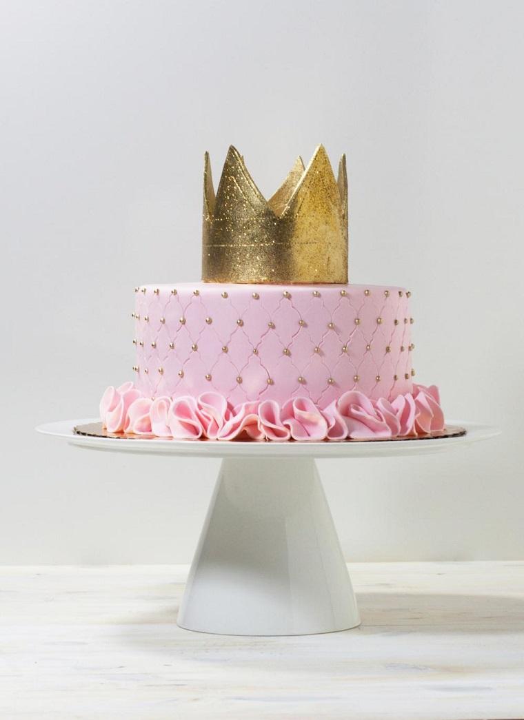 Torte di compleanno particolari, decorazione con pasta di zucchero e crema pasticcera rosa, corona in oro e palline