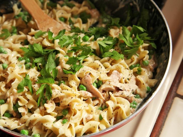 Cena veloce, pasta con tonno e prezzemolo tritato, tegame di colore rosso e mestolo di legno
