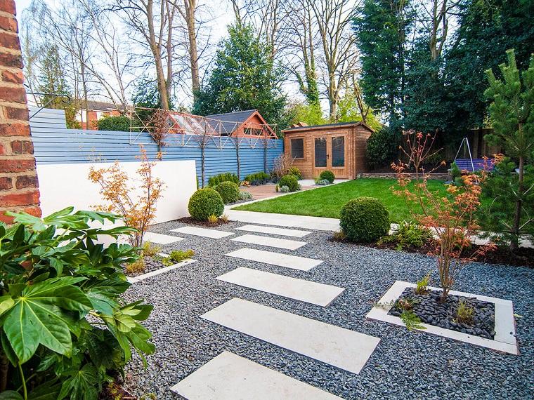 Idee per abbellire il giardino, pavimentazione con ghiaia e lastre di cemento, casetta di legno e prato verde