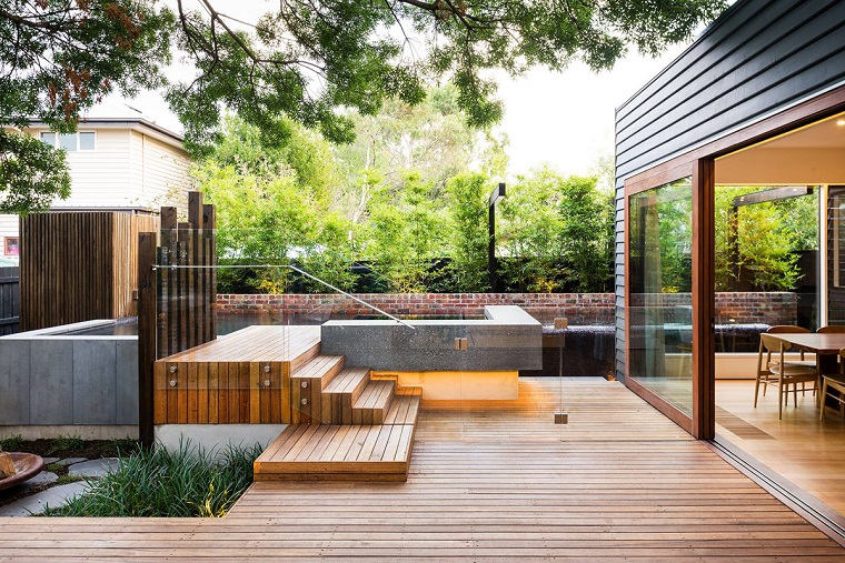 Idee giardino fai da te, pavimento in legno e una ringhiera in vetro, recinzione con siepe verde