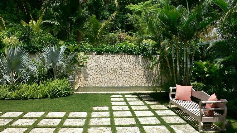 Giardini idee da copiare, piante tropicali e un arredo semplice con panchina in legno