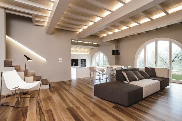 open space mobili moderni stile essenziale, divano tortura e beige, tavolo bianco e pavimento in parquet