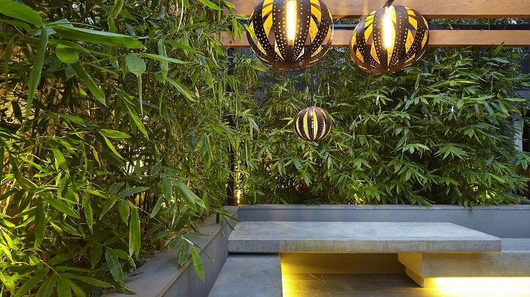 Come abbellire un giardino, parete con piante sempreverdi e lampade a sospensione