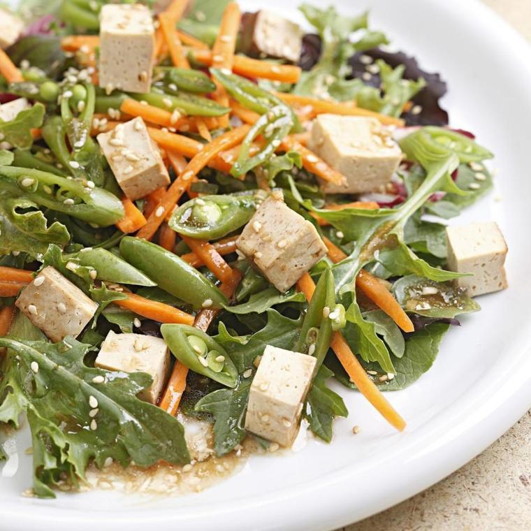ricetta estiva a base di tofu a cubetti, carote tagliate fini, piselli e insalata