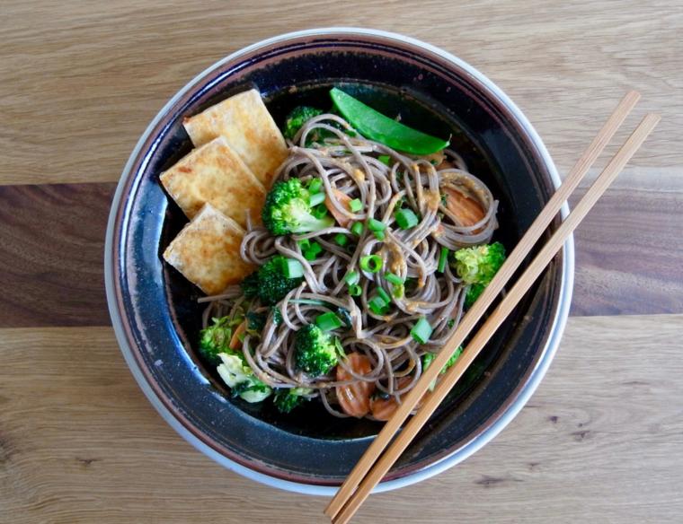 noodle serviti con delle fette di tofu e verdure: broccoli, carote e piselli