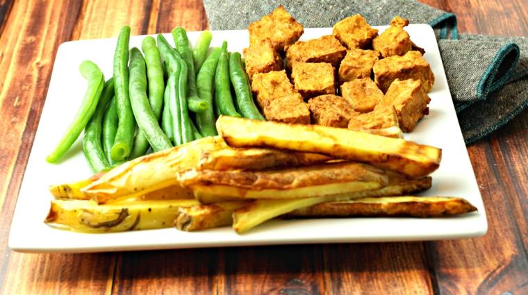 ricetta con del formaggio molle in panetti, feta a cbetti, piselli e patate arrosto