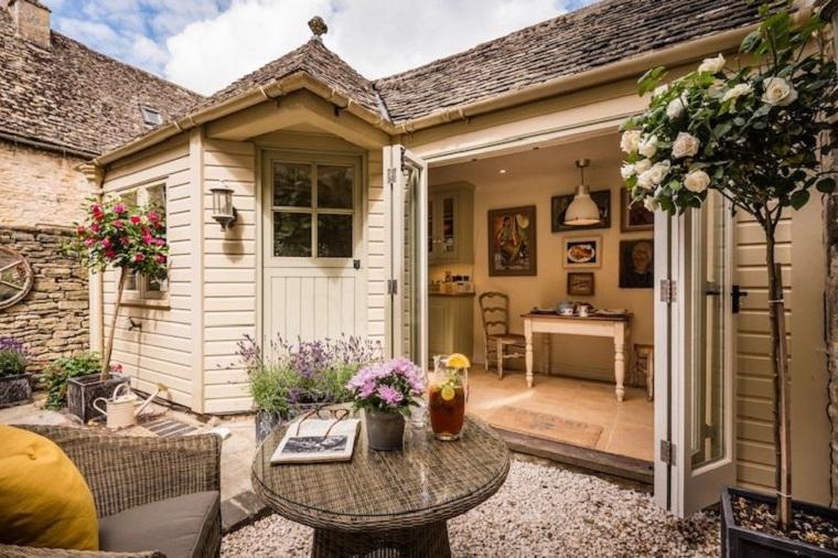 Idee giardino piccolo con pavimento in ghiaia, casetta in legno e mobili in rattan