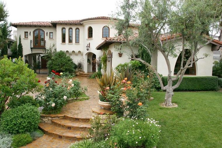 Giardini da copiare, casa molto grande con un patio verde e alberi, siepe e rose sui bordi del camminamento
