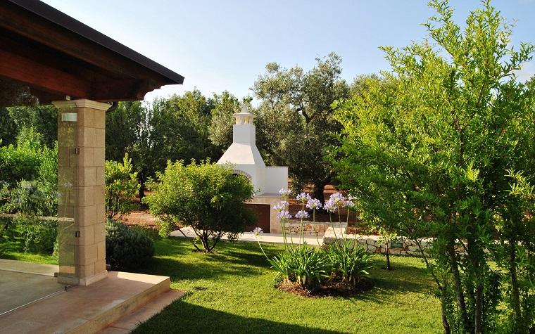 Idee giardino con barbecue in muratura, prato verde con piante sempreverdi e alberi