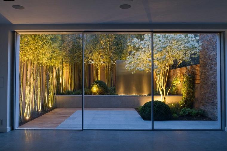 Idee giardino stile giapponese, pavimento in cemento e un albero in fioritura, illuminazione soffusa