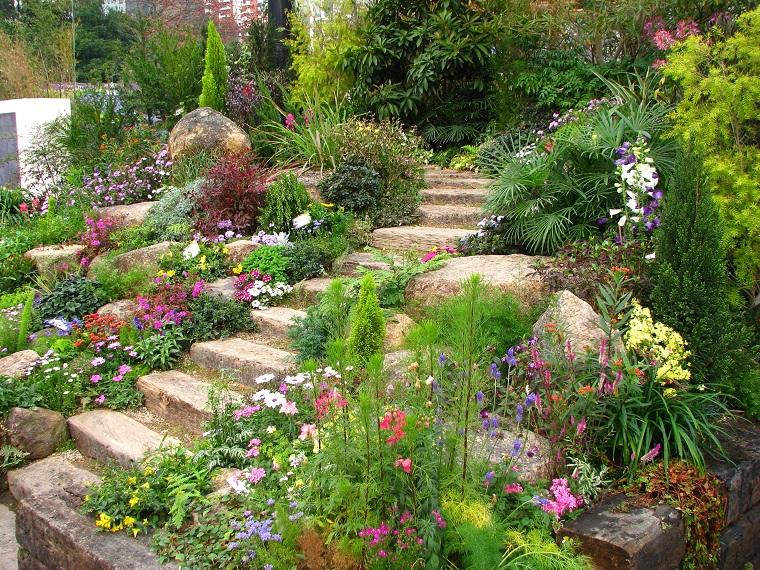 Giardino in pendenza con scalini in pietra, tanti fiori e piante sempreverdi